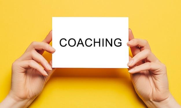 Des mains féminines tiennent du papier cartonné avec du texte coaching sur fond jaune. concept commercial et financier