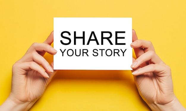 Des mains féminines tiennent du papier cartonné avec du texte partagez votre histoire sur un fond jaune.