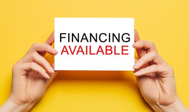 Des mains féminines tiennent du papier cartonné avec texte financement disponible sur fond jaune. concept commercial et financier