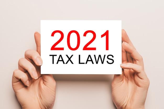 Des mains féminines tiennent du papier cartonné avec texte lois fiscales 2021 sur fond jaune. concept commercial et financier