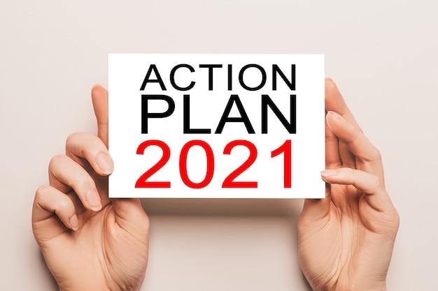 Des mains féminines tiennent du papier cartonné avec texte plan d'action 2021 sur fond jaune