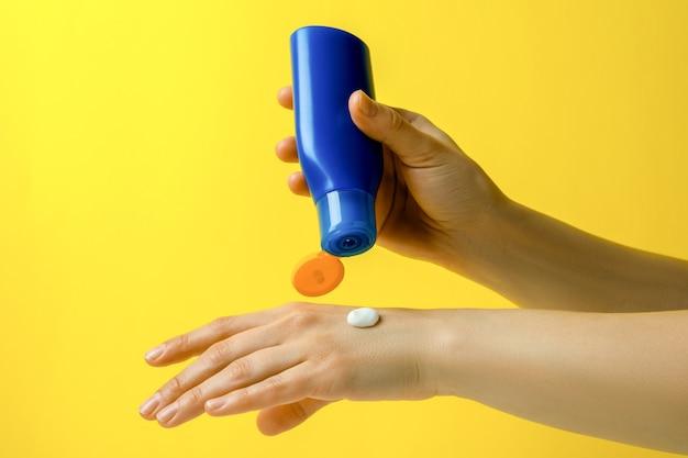 Les mains féminines tiennent un écran solaire sur jaune