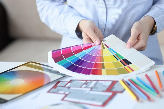 Des mains féminines tiennent un éventail de palette de couleurs
