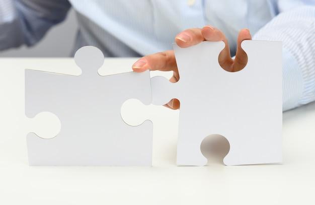 Des mains féminines tiennent de grands puzzles en papier blanc. concept de solution, stratégie et réalisation des objectifs, gros plan