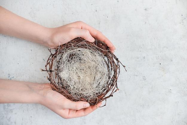 Des mains féminines tiennent un nid vide avec des oeufs de pâques colorés. composition abstraite de la vue horizontale supérieure. abstrait