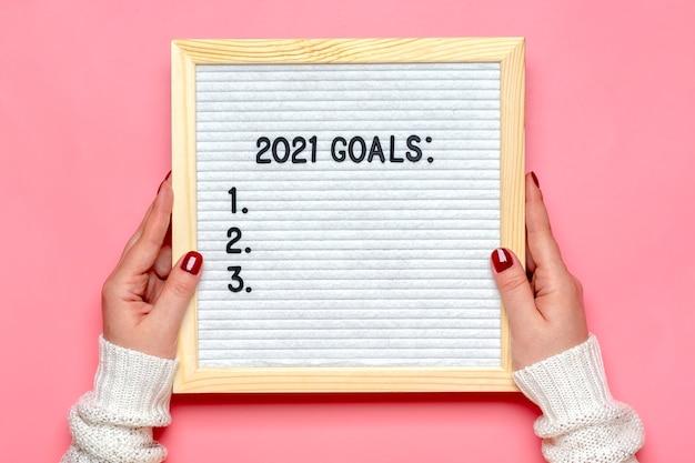 Des mains féminines tiennent un panneau de feutre avec texte - objectifs 2021 sur rose