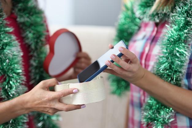Les mains féminines tiennent et passent la boîte festive avec smartphone