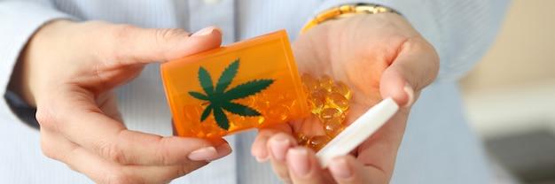 Les mains féminines tiennent un pot de pilules de marijuana propriétés médicinales du concept de marijuana