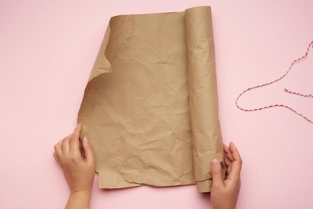 Des mains féminines tiennent un rouleau de papier brun