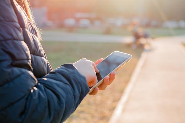 Des mains féminines tiennent un smartphone et un sms à l'extérieur sous les rayons du soleil du soir. la navigation sur internet
