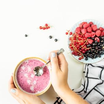 Des mains féminines tiennent un smoothie aux fruits dans un bol à côté d'une assiette de framboises