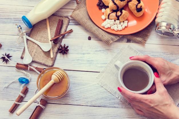 Des mains féminines tiennent une tasse de café