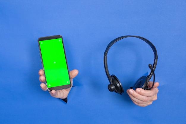 Des mains féminines tiennent un téléphone noir avec un écran vide et des écouteurs sur fond bleu. les femmes sont insérées dans un fond de papier. écran clé chroma du téléphone. place pour une inscription.