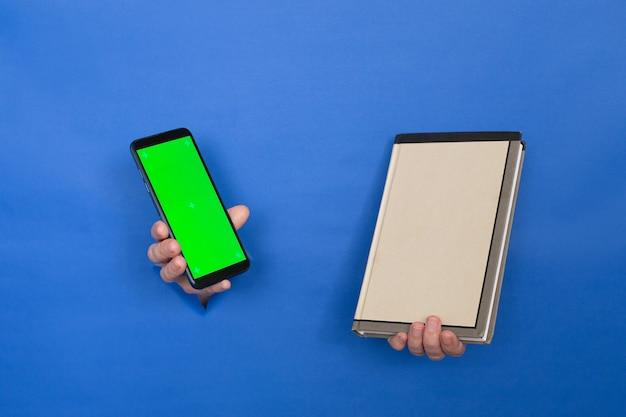 Des mains féminines tiennent un téléphone noir avec un écran vide et un livre sur fond bleu. les femmes sont insérées dans un fond de papier. touche d'écran de téléphone chrome. place pour une inscription.
