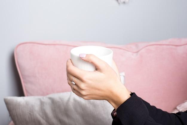 Des mains féminines tiennent le thé dans une tasse en céramique blanche dans un intérieur rose