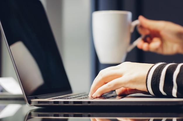 Mains féminines en train de taper sur le clavier d'un ordinateur portable tout en tenant une tasse de café, en travaillant à la maison concept