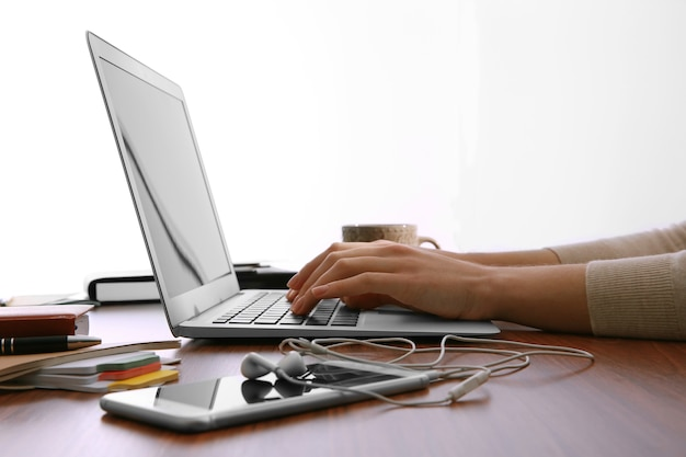 Mains féminines travaillant avec un ordinateur portable au bureau sur fond de fenêtre