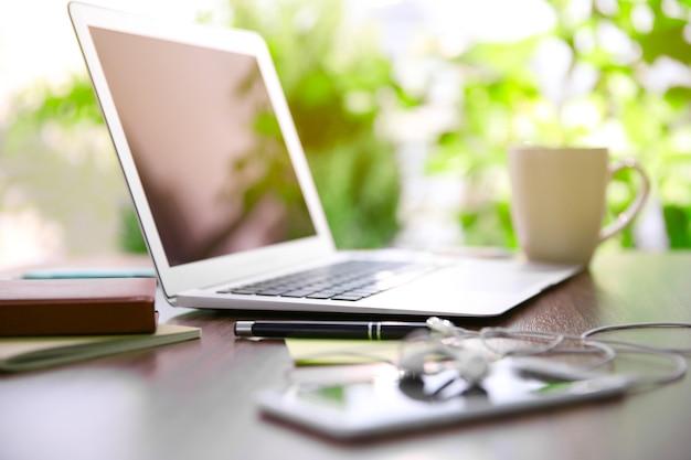 Mains féminines travaillant avec un ordinateur portable en plein air sur fond de plante verte floue