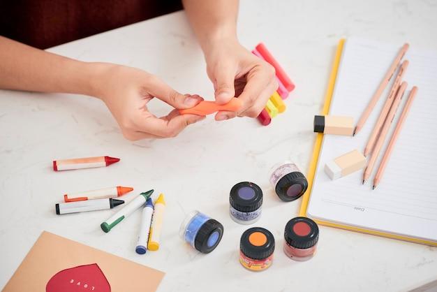 Mains féminines travaillant avec de la pâte polymère. le processus de travail avec le plastique sur fond blanc.