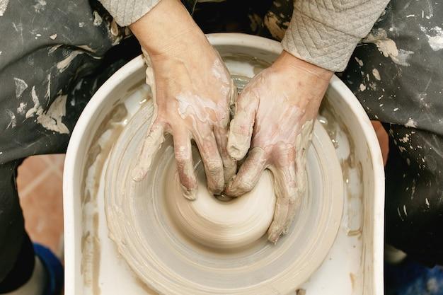 Mains féminines travaillant sur le tour de poterie