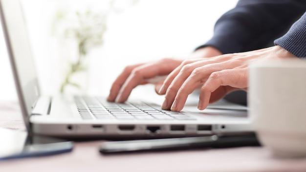 Les mains féminines travaillent sur le clavier de l'ordinateur portable.