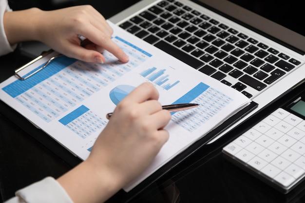 Des mains féminines travaillent avec graphique sur de cahier