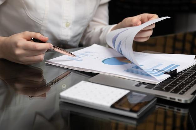 Des mains féminines travaillent avec graphique sur fond de cahier