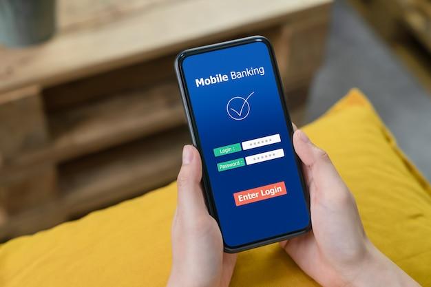 Mains féminines utilisant les services bancaires mobiles sur le téléphone et entrez le mot de passe pour vous connecter à l'application.
