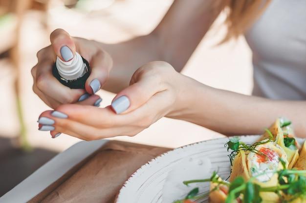 Les mains féminines utilisent un antiseptique antibactérien pour désinfecter les mains