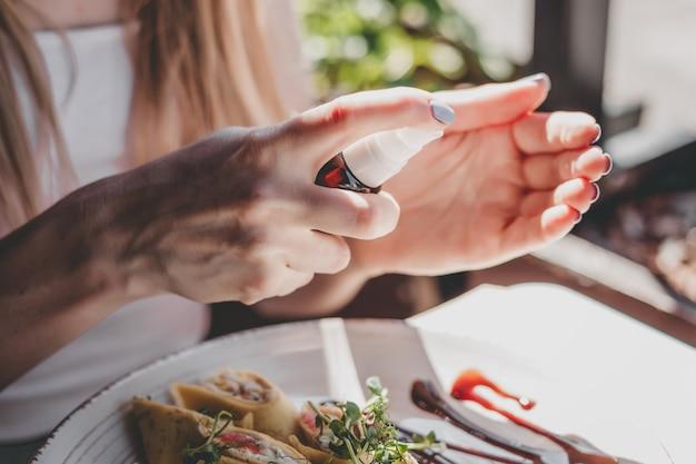 Les mains féminines utilisent un antiseptique pour se nettoyer les mains