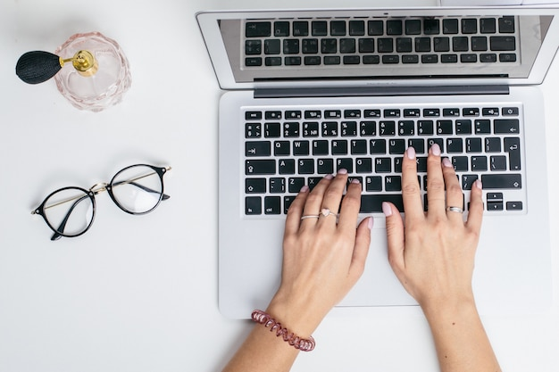 Des mains féminines utilisent un clavier d'ordinateur portable sur une table blanche