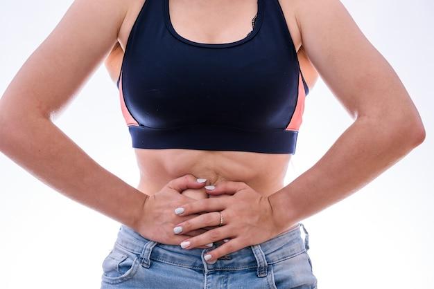 Mains féminines sur le ventre, concept de douleur isolé sur blanc