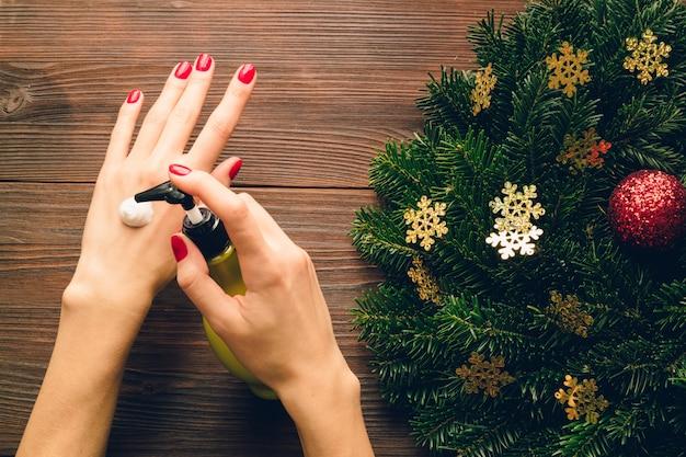 Mains féminines avec vernis à ongles rouge appliquée crème pour les mains