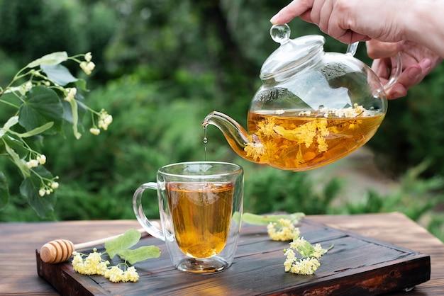 Mains féminines versant du thé de tilleul d'une théière en verre dans une tasse dans le jardin, tisane saine, gros plan.