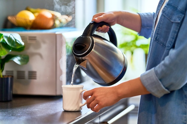 Mains féminines versant de l'eau bouillante à partir d'une bouilloire en métal inoxydable moderne dans une tasse en verre pour préparer du thé dans la cuisine à la maison