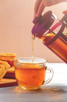 Des mains féminines versent le thé de la bière dans une tasse sur une table en bois blanche avec gaufres.