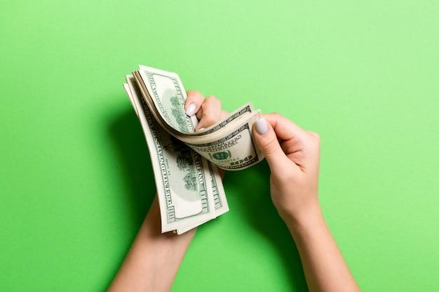 Mains de femme d'affaires comptant des billets de cent dollars sur fond colful. salaire et salaire concept. vue de dessus du concept d'investissement