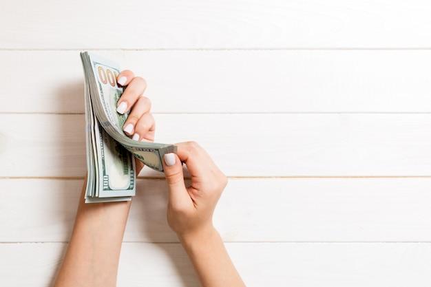 Mains de femme d'affaires comptant des billets de cent dollars. salaire et salaire concept avec espace de copie. vue de dessus du concept d'investissement