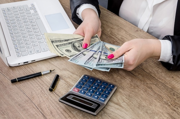 Mains de femme d'affaires comptant les billets en dollars