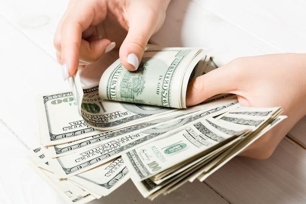 Mains de femme d'affaires comptant cent billets d'un dollar sur fond de bois
