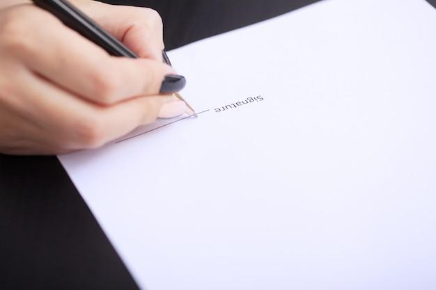 Mains de femme d'affaires signant le contrat