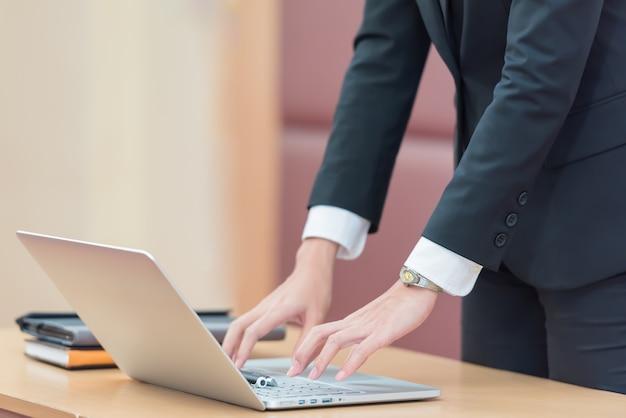 Mains de femme d'affaires en tapant sur le clavier d'ordinateur portable au bureau.
