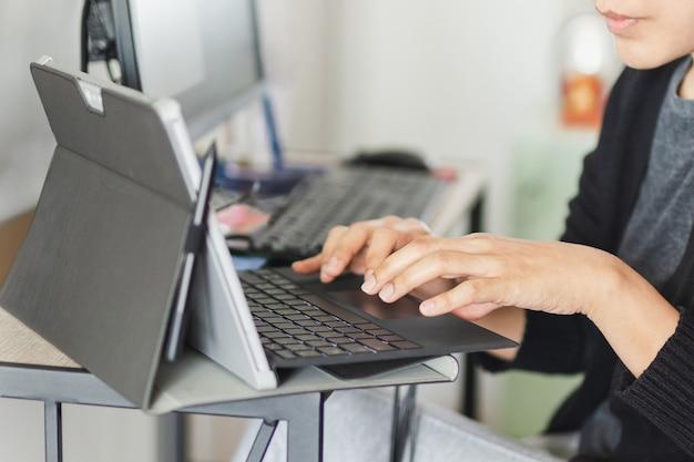Mains de femme d'affaires tapant sur clavier d'ordinateur portable à la maison.