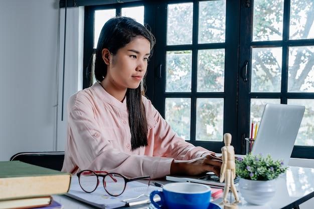 Mains de femme d'affaires tapant sur le clavier et travaillant sur ordinateur portable au bureau.
