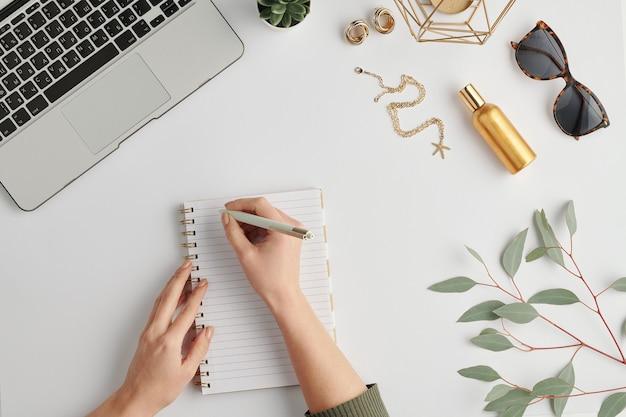 Mains de femme d'affaires tenant un stylo sur une page vierge de l'ordinateur portable entouré de divers trucs