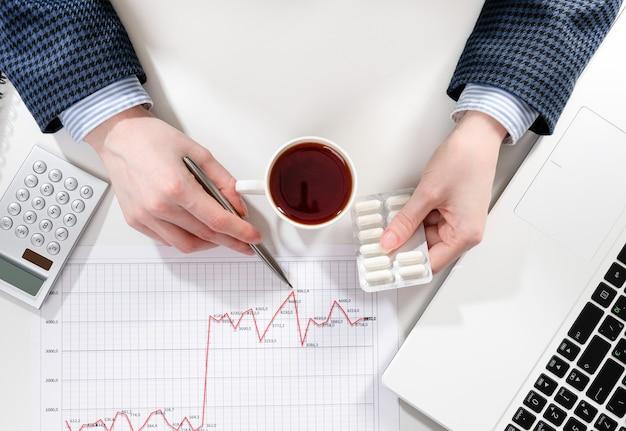 Mains d'une femme d'affaires travaillant avec des graphiques commerciaux sur le bureau au bureau