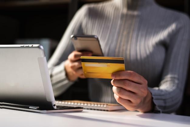 Mains de femme d'affaires utilisant un smartphone et tenant une carte de crédit assise. concept de paiements d'achats en ligne.