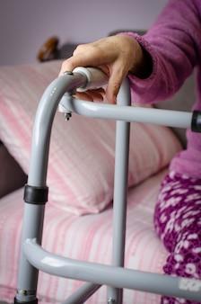 Mains d'une femme âgée sur les poignées d'une marchette.