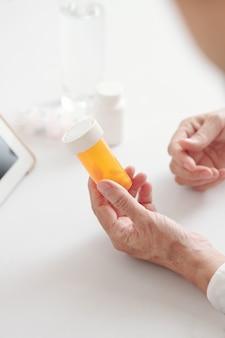 Mains de femme âgée tenant une bouteille de pilules en plastique avec des analgésiques ou des suppléments