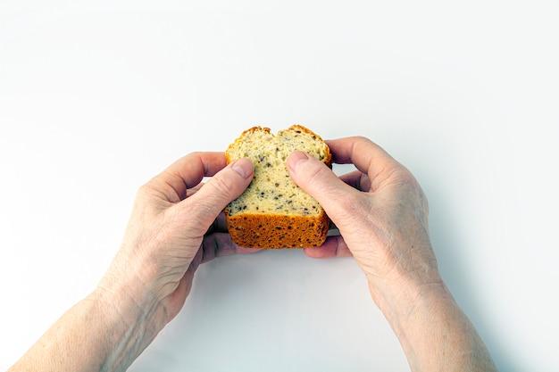 Les mains d'une femme âgée tiennent un petit pain de grains entiers fait maison fraîchement cuit sur fond blanc. concept de main secourable, image tonique